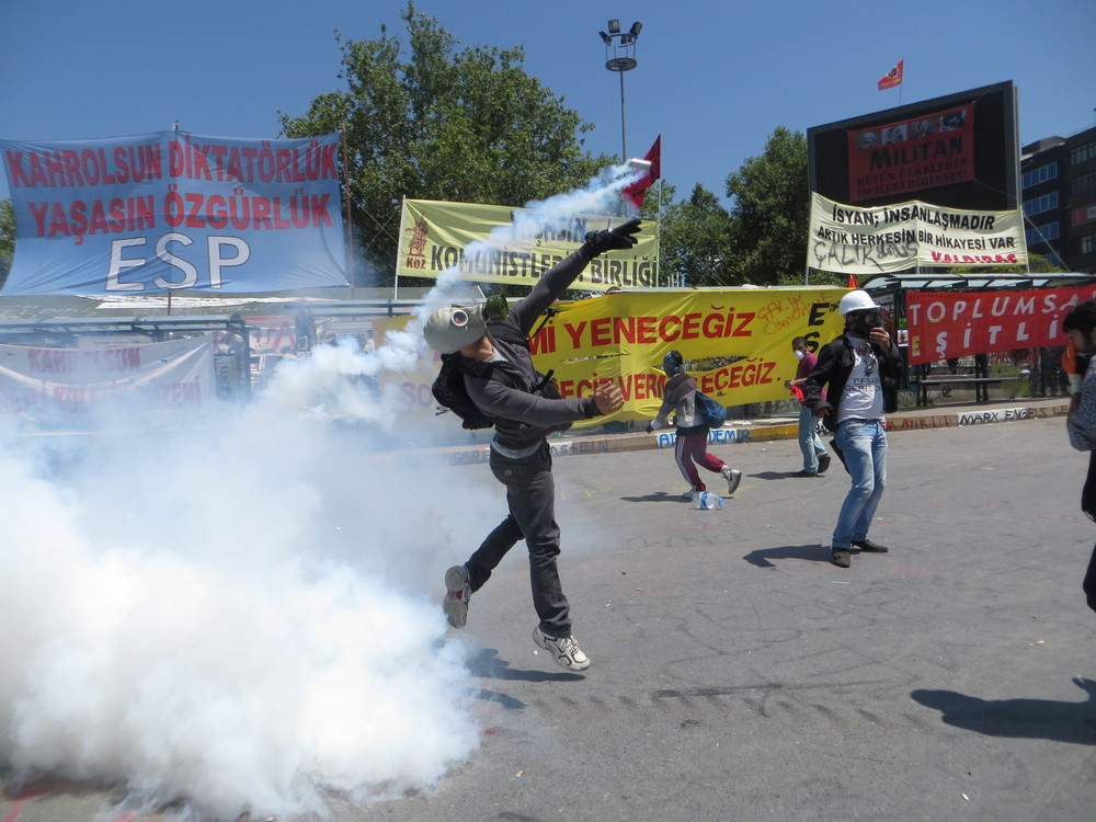 A protester returns a tear gas canister in Taksim Square.