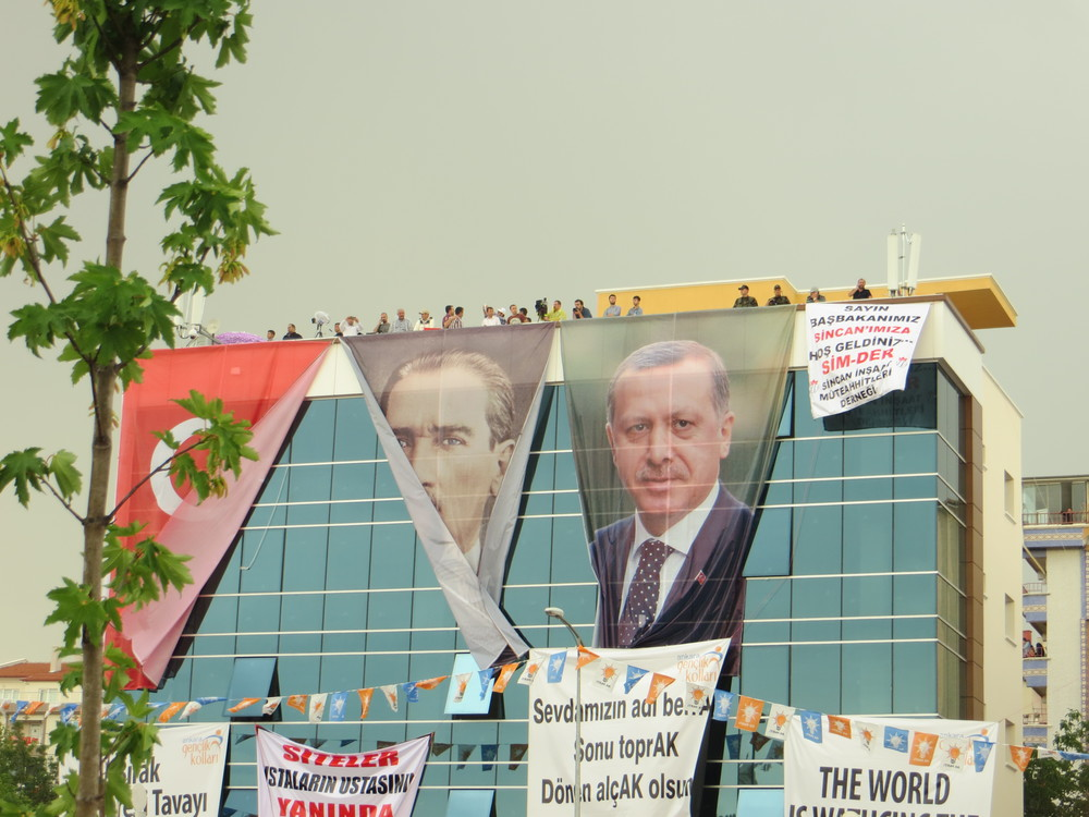The AKP rally in Ankara. Even the Turkish flag seems less important to properly hang than the portrait of Erdogan. Ataturk's portrait was actually half-furled, with the two bottom corners both stuffed through an open window.