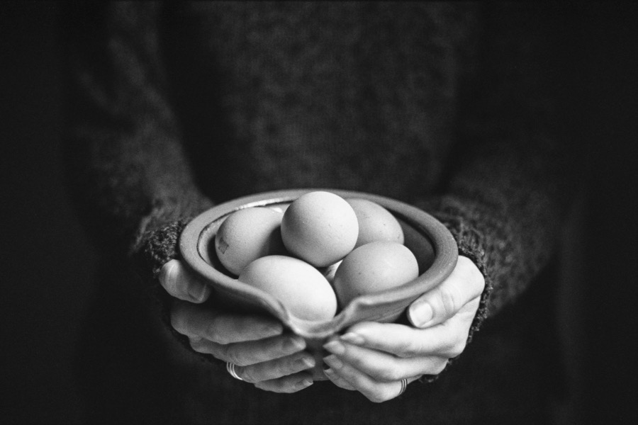 a bowl of eggs held by a woman at arms length