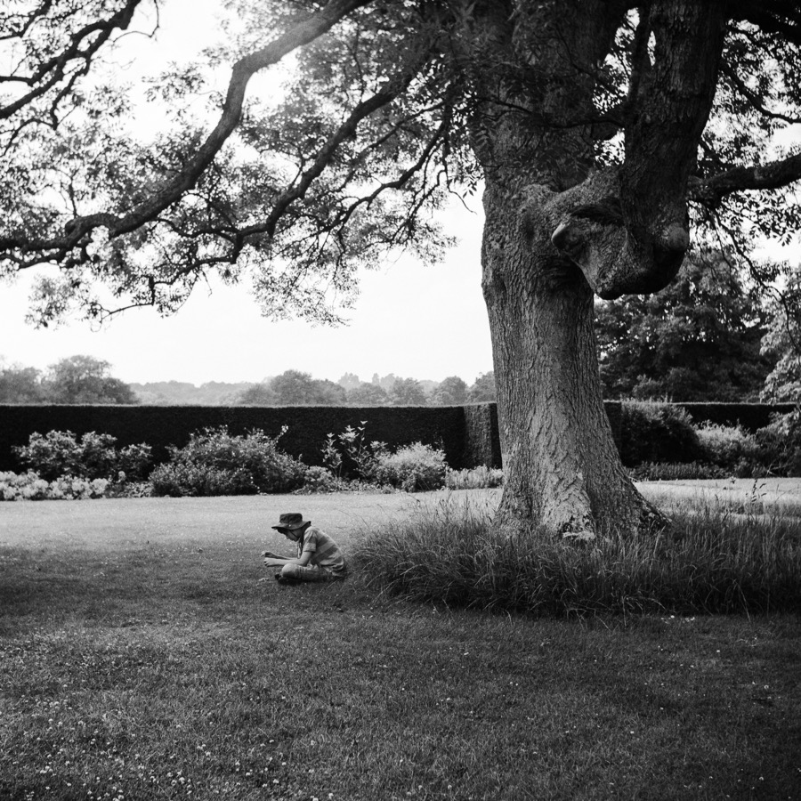 A young boy sitting under a tree at National Trust property Batemans,
