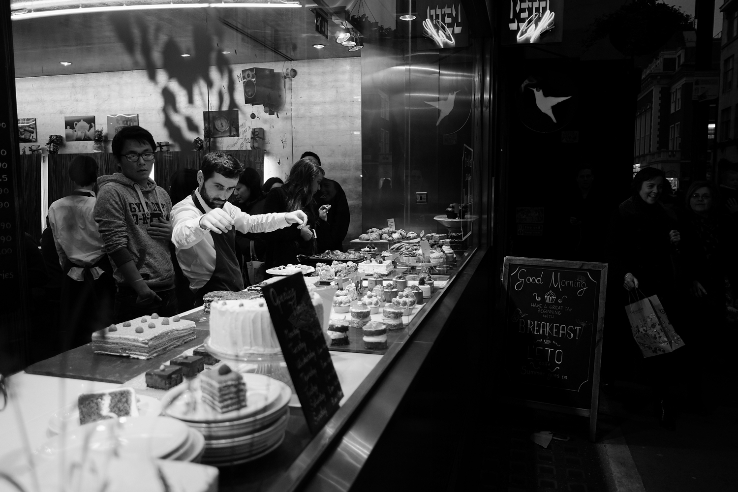 Fujifilm X-T1 jpeg file of a patisserie shop worker admiring his wares
