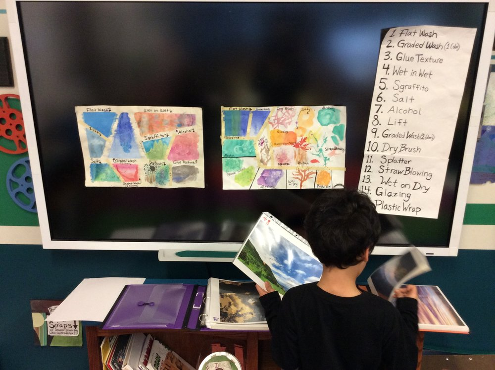 A student selects their sky photo from a binder full of diverse, beautiful skies. We have also learned about different types of clouds during this unit.