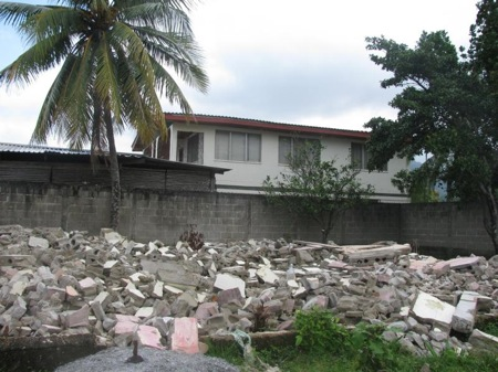 Photo caption: The ruins of a house in Rio Negro, with one of the last houses standing in the backdrop at the location where the Banana Coast cruise ship terminal is now located. Picture taken in 2011.