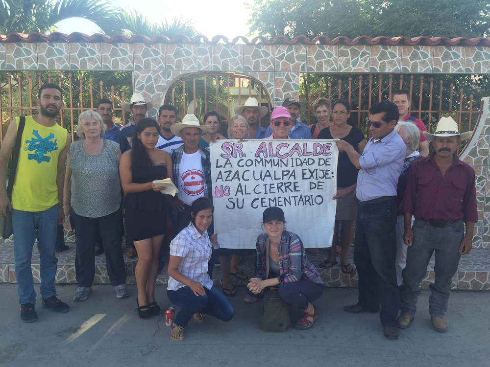 "In front of the house of the mayor of La Unión, Copan with community members and environmentalists from the community of Azacualpa that are fighting to protect their 200-year old cemetery under threat by the expansion of Canadian mining company, Aura Minerals. Sign reads: ""Mr. Mayor. The community of Azacualpa demands: no to the closure of their cemetery."""
