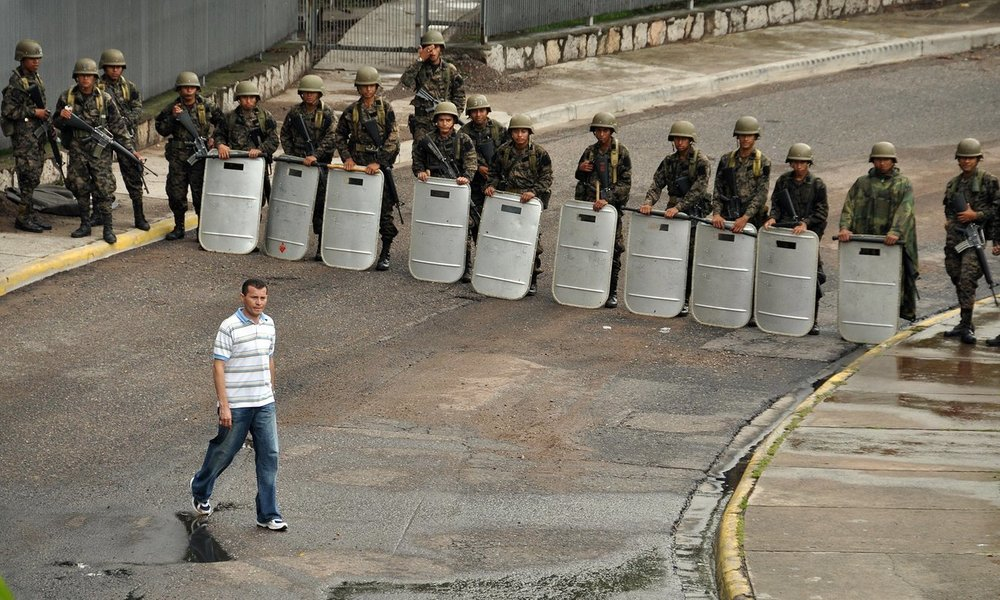 A pedestrian walks past a row of soldiers near the presidential palace following a coup d'etat that saw President Manuel Zelaya ousted in Tegucigalpa on 28 June 2009. Photograph: Yuri Cortez/AFP/Getty Images