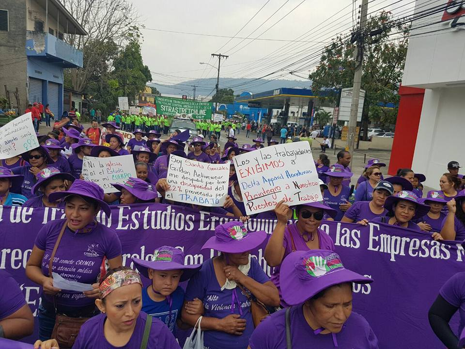 "May Day March 2017. Paper sign to the right reads ""Male and female workers demand that Delta Apparel Honduras give us our jobs back."" Photo credit: CODEMUH"