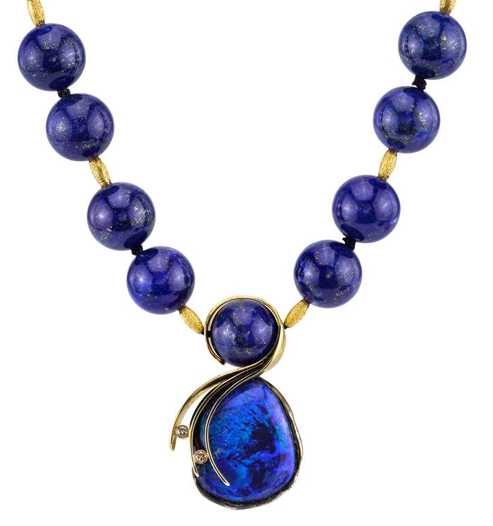 Reminiscent of deep blue, Mediterranean waves flirting with the golden sands, this necklace is a showstopper. An extravagant Lightning Ridge Opal hangs from an 18 Karat Yellow Gold chain studded with natural Lapis Lazuli beads. The pendant, accented with 20 Karat Yellow Gold and White Diamonds, is a work of art within itself.