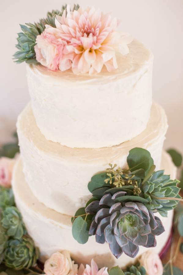White cake with flowers and succulents