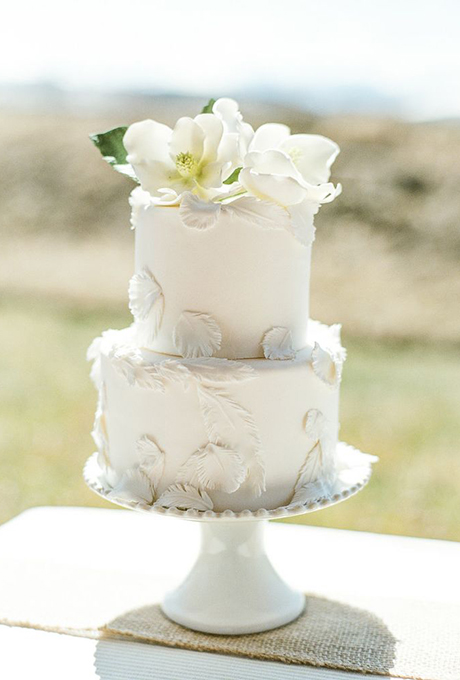 White cake with feathers and flowers