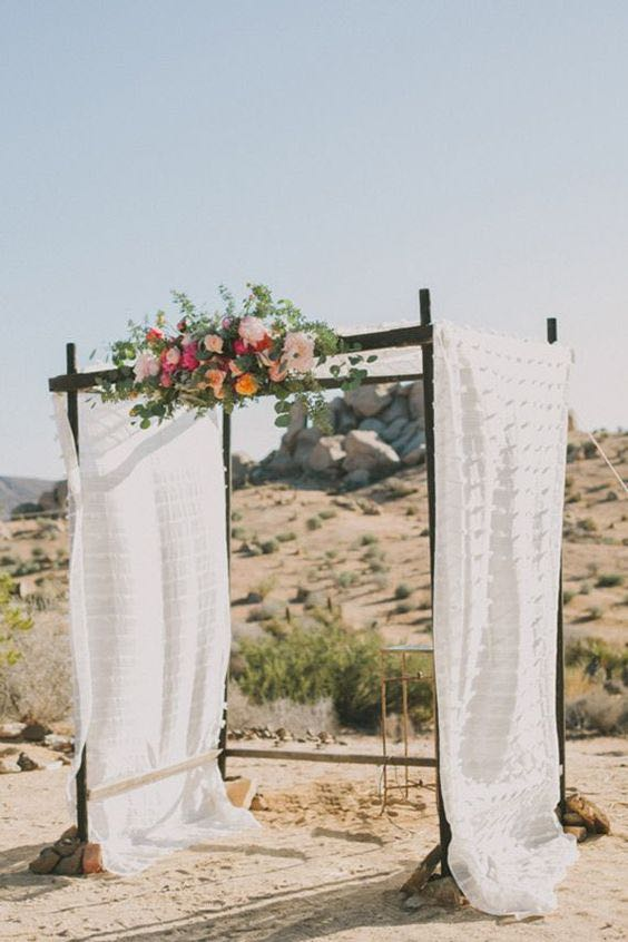 Wedding Arch with Flowers and White Fabric