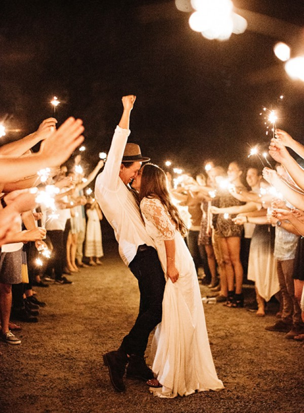 Bride and Groom Kissing with Guests and Sparklers