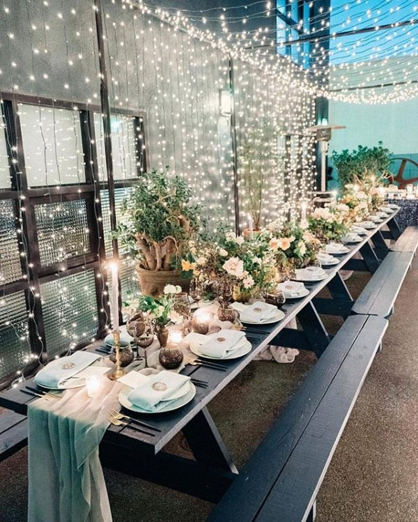 Outdoor Dining Tablescape with Flowers and Twinkle Lights