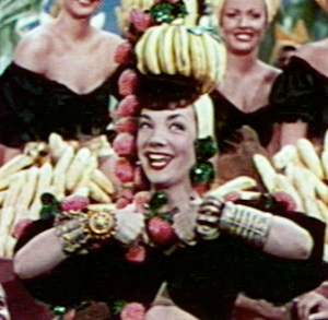 Photo Source: https://en.wikipedia.org/wiki/Fruit_hat#/media/File:Carmen_Miranda_in_The_Gang%27s_All_Here_trailer_cropped.jpg