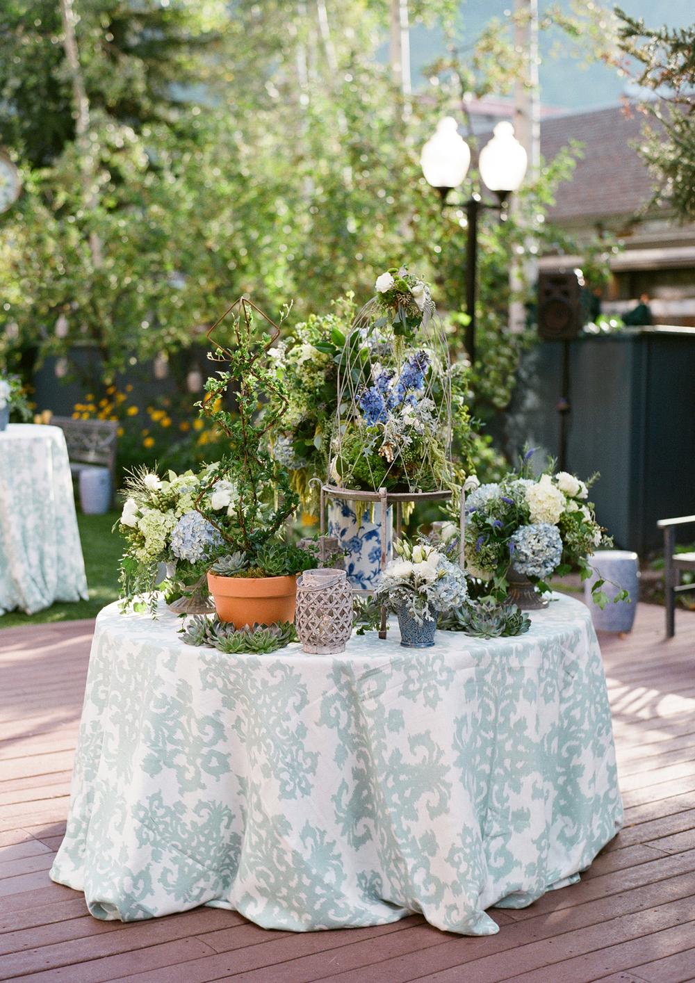 Table with blue, white, green flower arrangements
