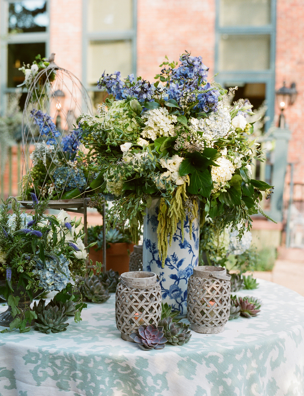 Green, white, blue flower arrangements on table