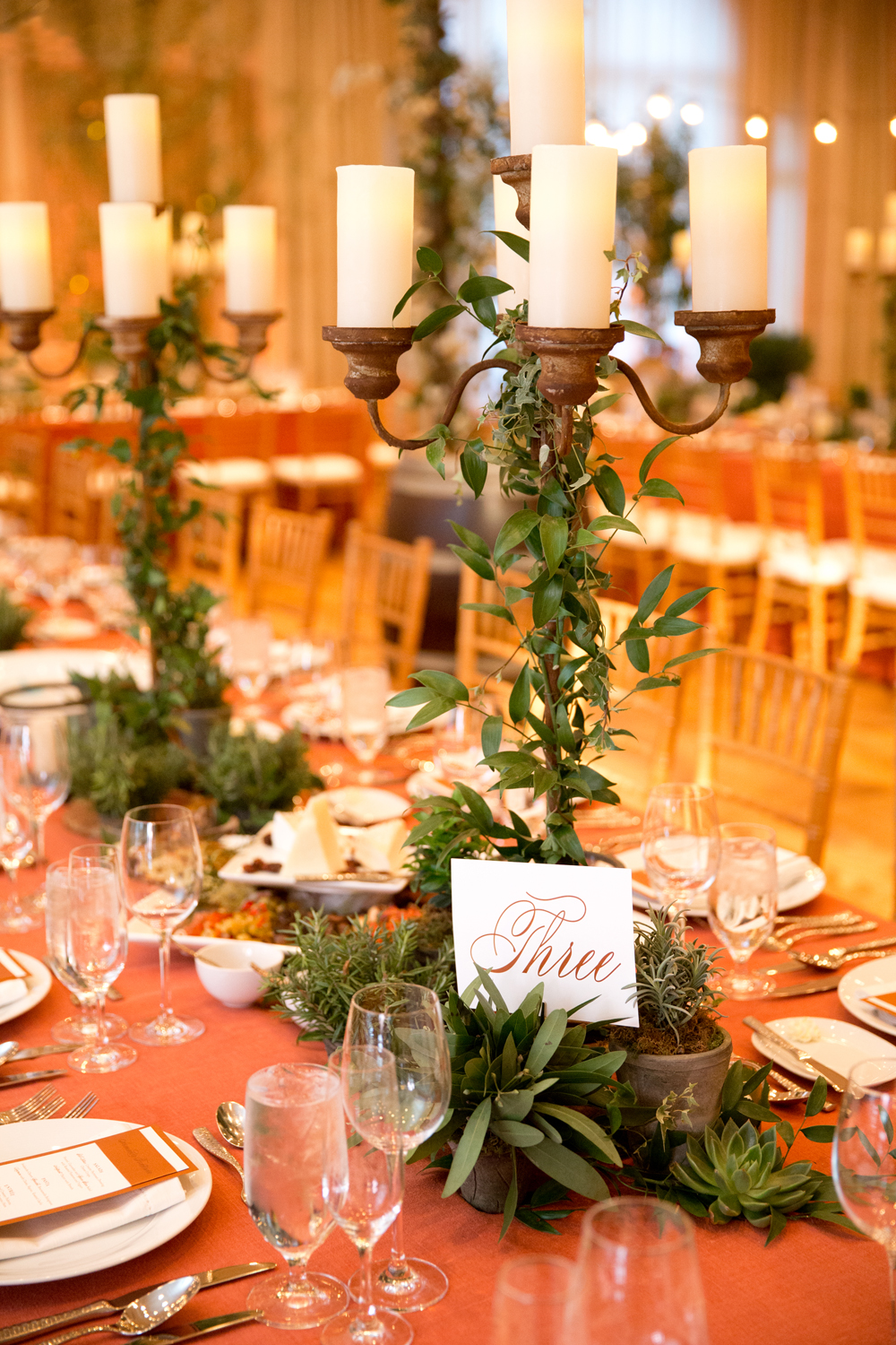 Greenery wrapped candle sticks on dinner table