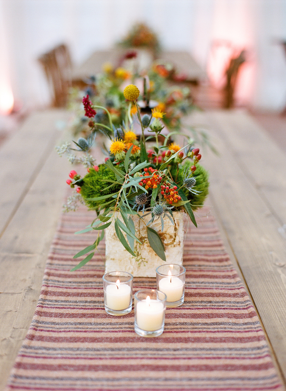 Wildflower centerpieces wrapped in aspen tree bark