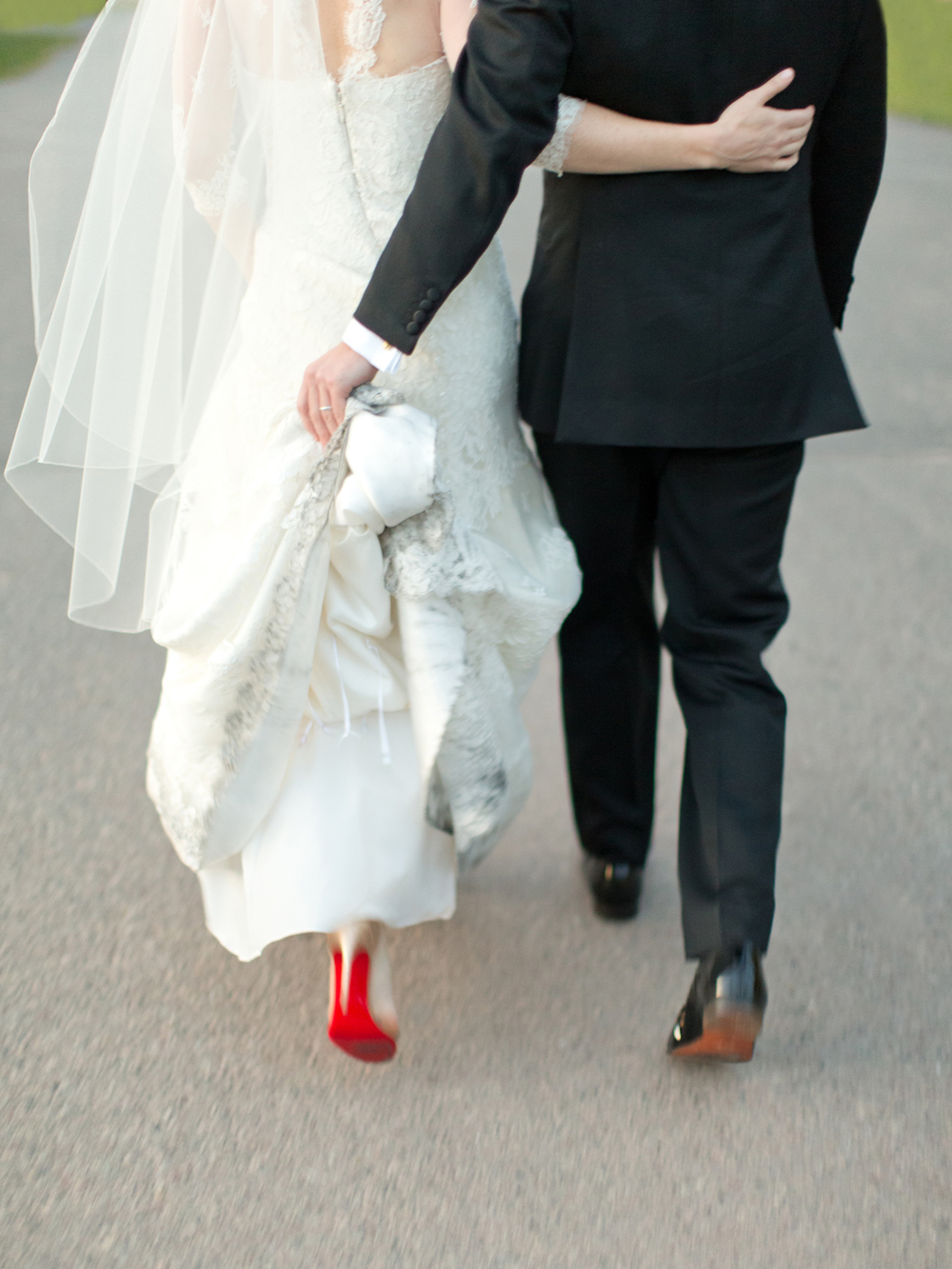 Bride and groom walking with groom holding dress train