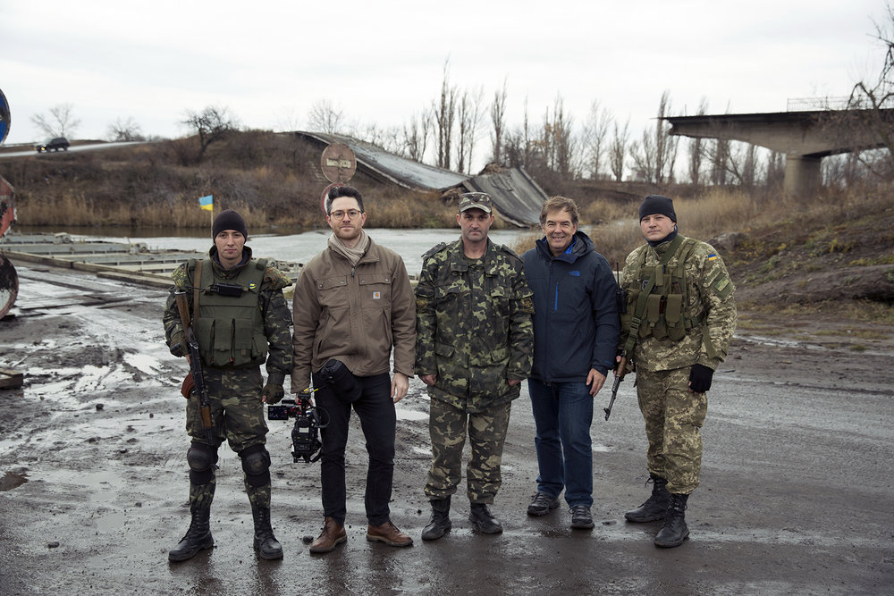 Ukrainian soldiers and crew pose in front of a bridge destroyed during fighting in eastern Ukraine.