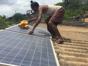A worker for Onergy, a social enterprise in India, installs micro-grid solar panels on a school roof.