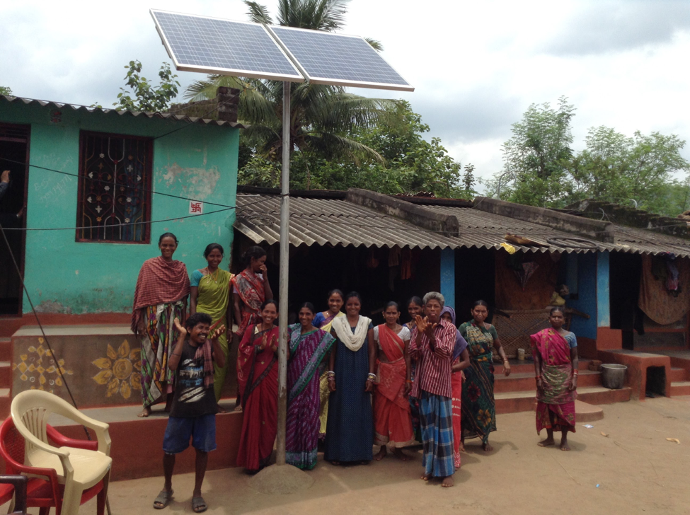 Residents in Sergarh stand behind a solar microgrid that provides power to the village.