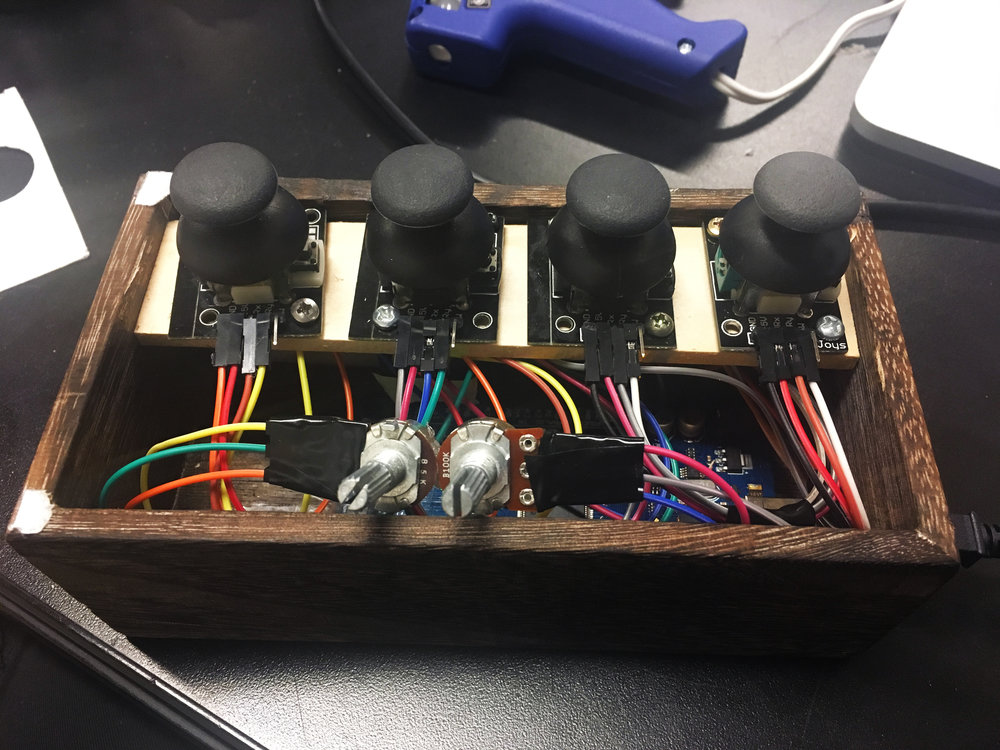 Controller box containing breadboard, Arduino, potentiometers, and joysticks