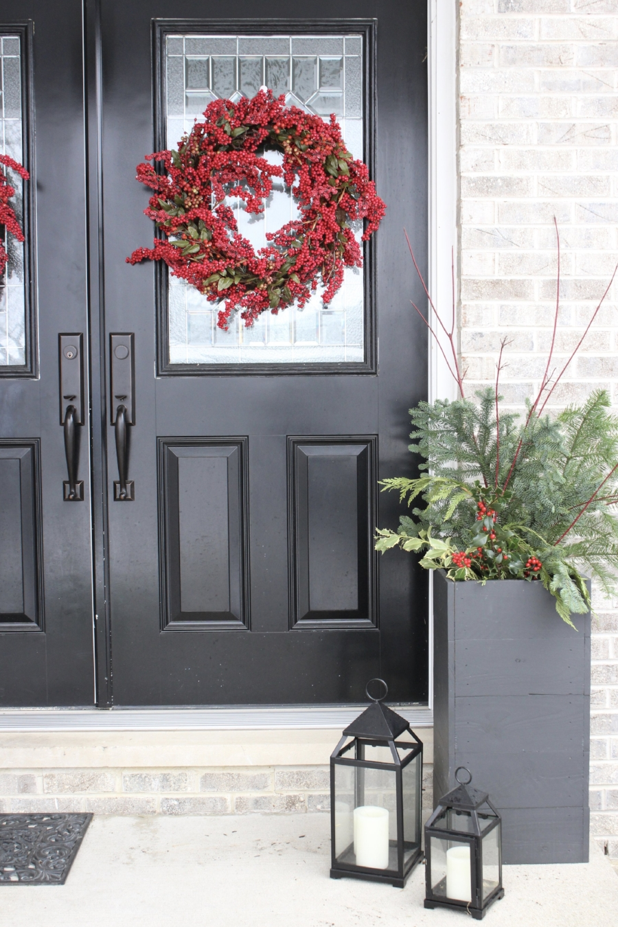 Porch planters with seasonal holiday greens- styling by Laura Design Co.
