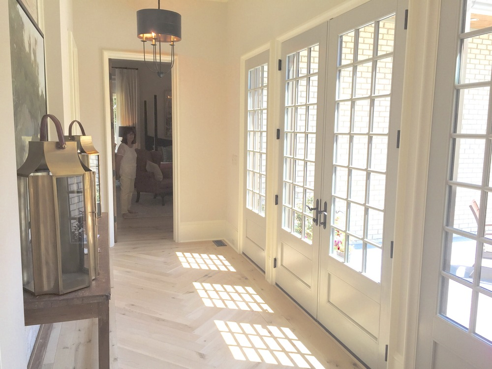Light abounded in this hallway overlooking a private patio. Soft colors were used including a taupe wall and light blue doors that complimented the raw hardwoods.