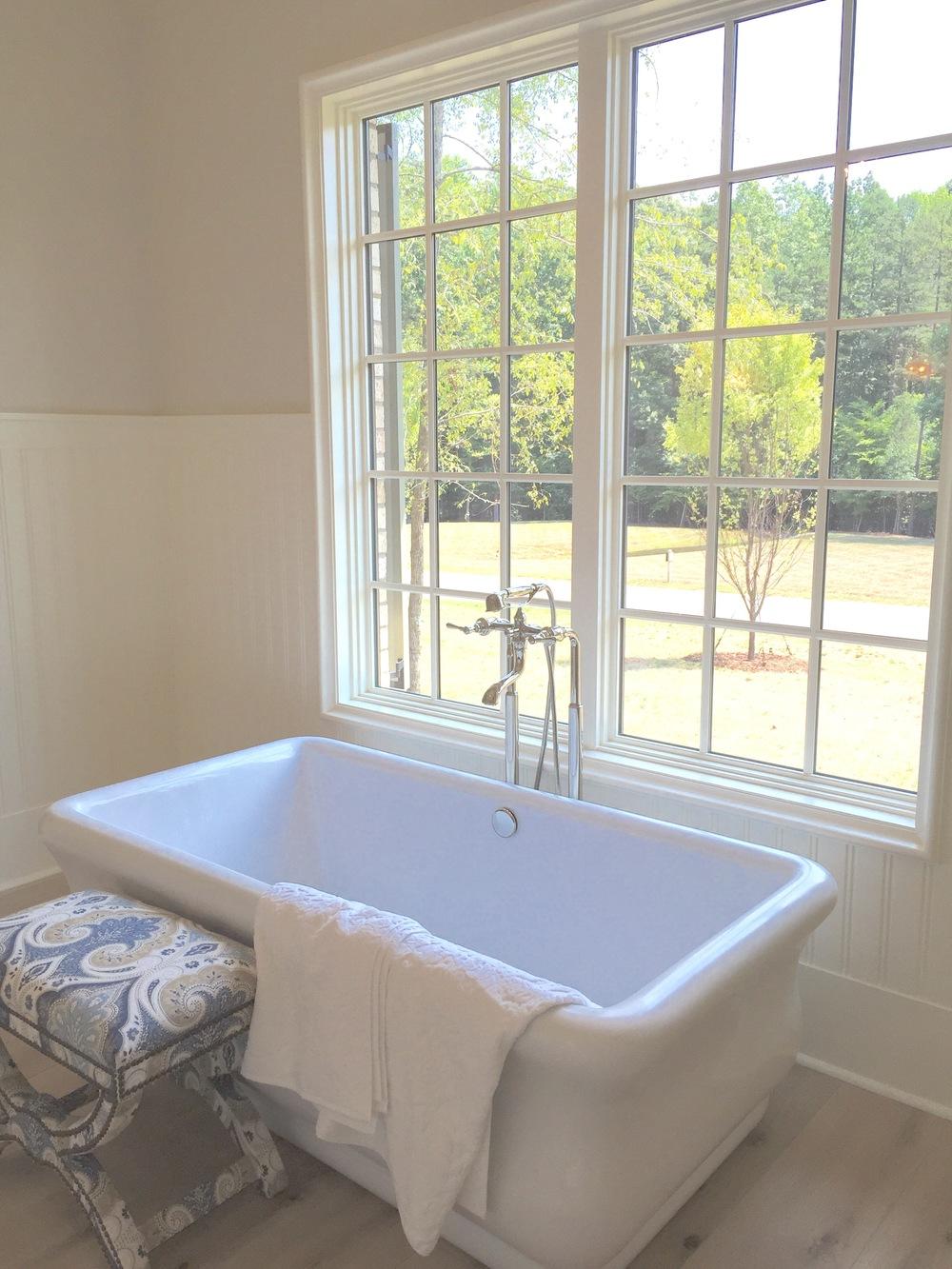 Bead board and plenty of natural light made this stand alone tub exceptional. An adorable paisley seat was paired next to the tub for a colorful touch.