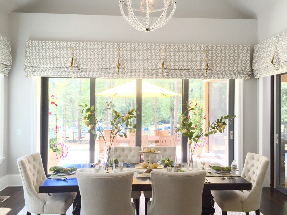 This grand breakfast room had an inviting 6 person table and magnificent views with windows on all three walls. Tall table accessories brought the eye up to a beautiful chandelier.