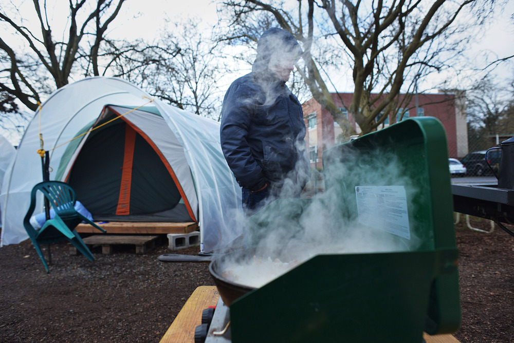 Eugene, Ore. - A transient resident of the Nightingale Health Sanctuary is hidden by steam from a pan of hash browns being cooked for a community breakfast. By: Debra Josephson