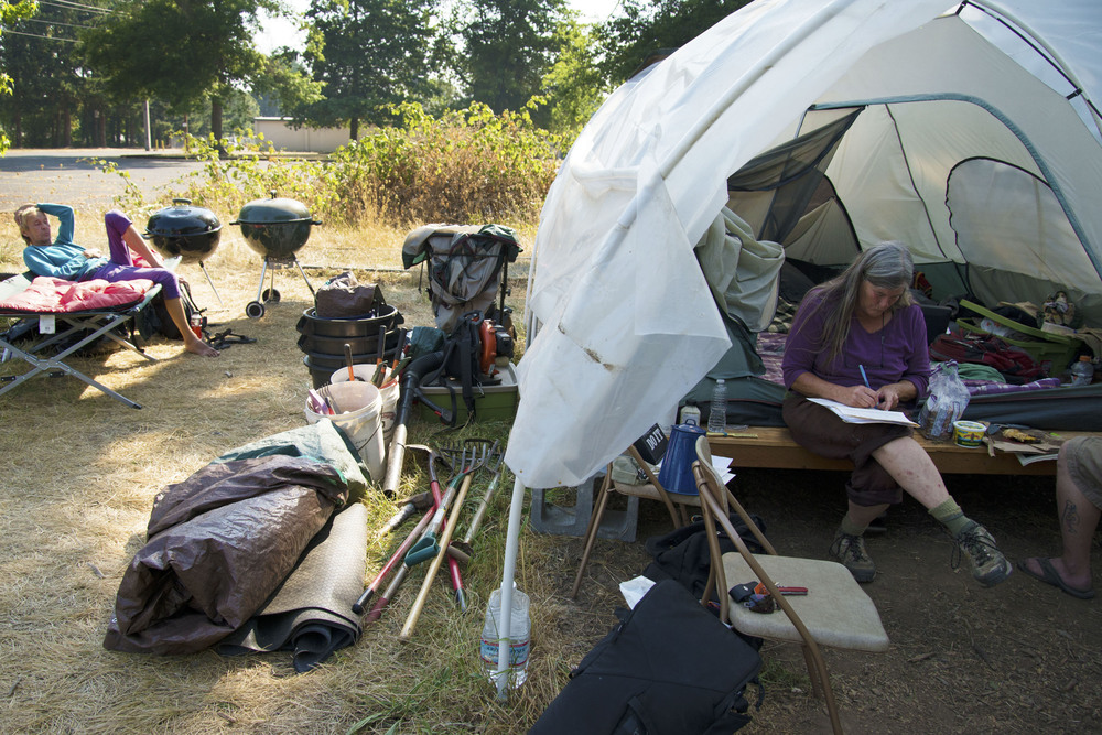 Eugene, ORE - Tracy Joscelyn prepares paperwork before moving camp. Rick Harrington, a new resident, relaxes while the camp is being packed up. By: Debra Josephson