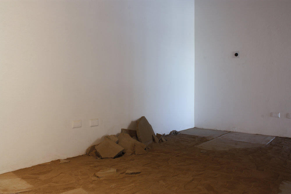 "towards a surface  (after entry)   Sifted earth dug from a 5'2"" x 2' x 1' area, recording emitted from a speaker, concrete, steel, saliva, and light   16'5"" x 7' x 14'  2017"