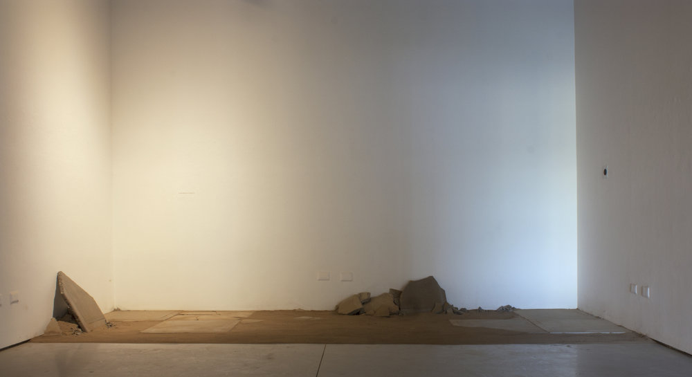 "towards a surface  (before entry)   Sifted earth dug from a 5'2"" x 2' x 1' area, recording emitted from a speaker, concrete, steel, saliva, and light   16'5"" x 7' x 14'  2017"