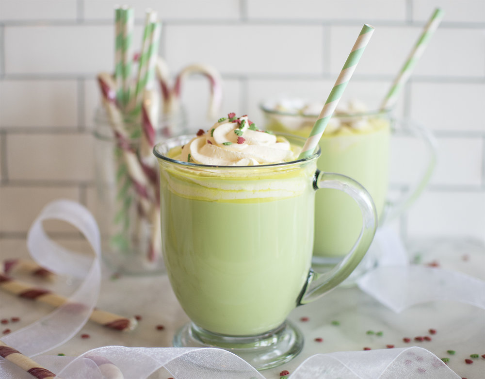 Grinch Hot Cocoa | Makes 4 Cups Recipe: 4 cups organic milk 2 T. + 2 tsp. (30 g.) organic sugar 2 T. (30 g.) organic white chocolate (for melting) chunks Holiday Tree Sprinkle Set Whipped Cream or Marshmallows (optional) Directions: In a medium pot, add the milk, sugar, white chocolate and green dye. Put over high heat and stir until temperature on a drink thermometer reaches 140-160 degrees. Remove from heat and pour into mugs. Top with marshmallows, whipped cram and Christmas Tree Sprinkles!