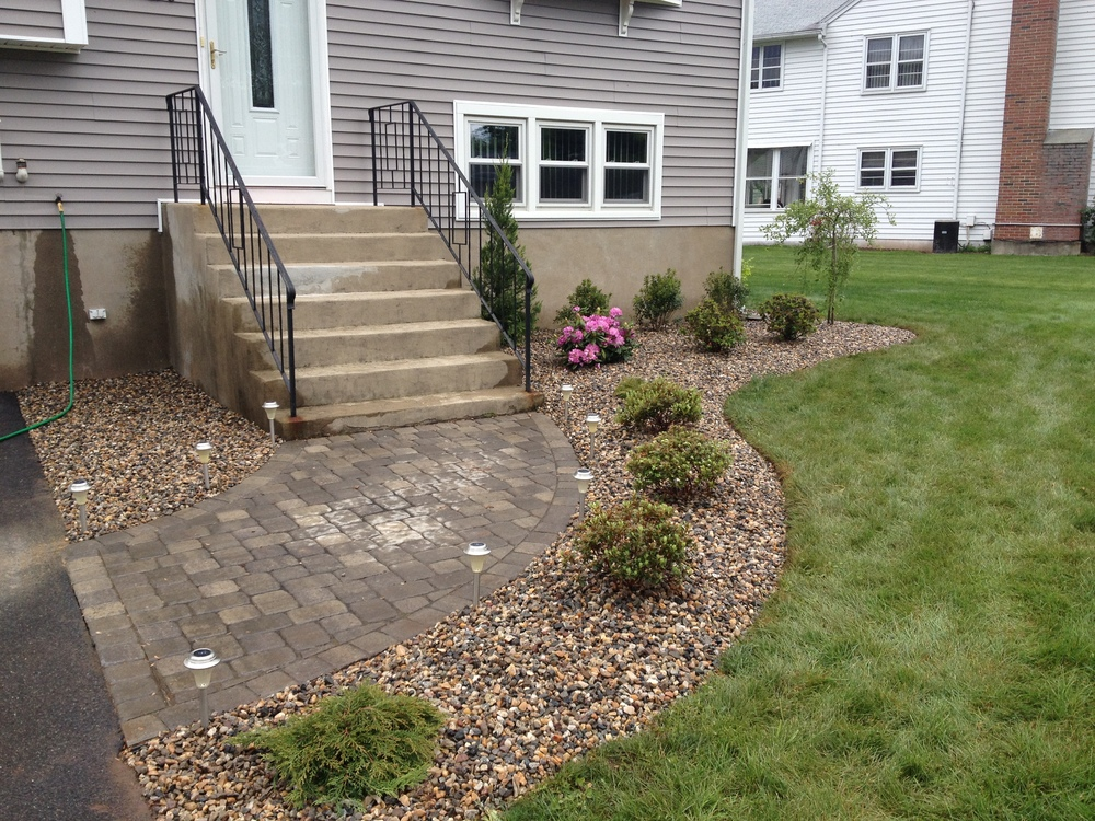 A front yard with new stairs leading up to a patio