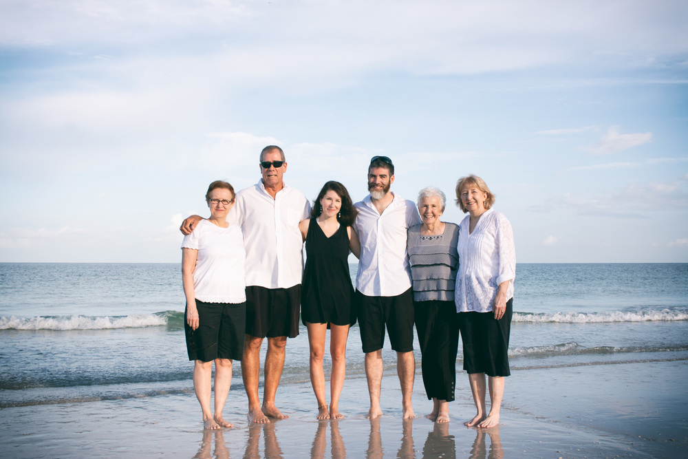 The family poses along the shore at Pass-a-Grille Beach.