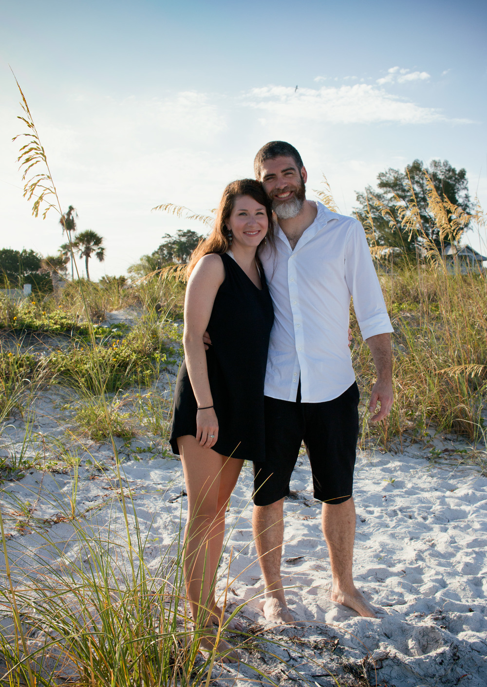 A cute couple pose amongst the white sand and grass at Pass-a-Grille Beach.