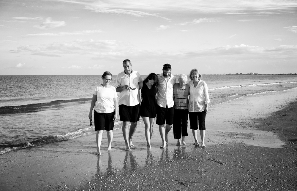 A black and white, candid family beach photo at Pass-a-Grille beach - the family walks along the shore.