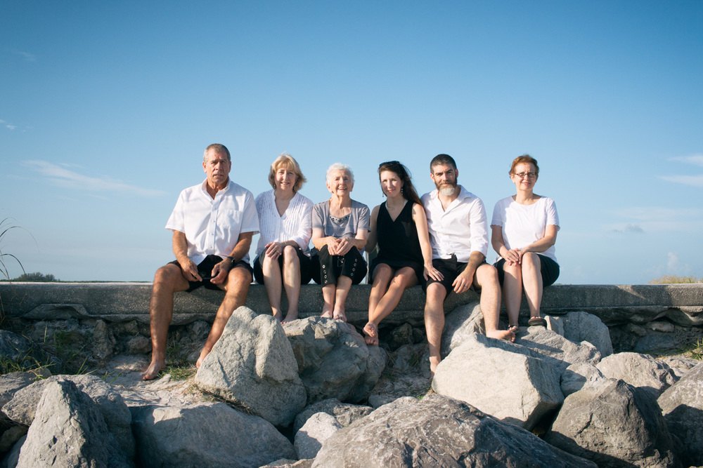 A family beach photo seated atop the rocks at Pass-a-Grille Beach.