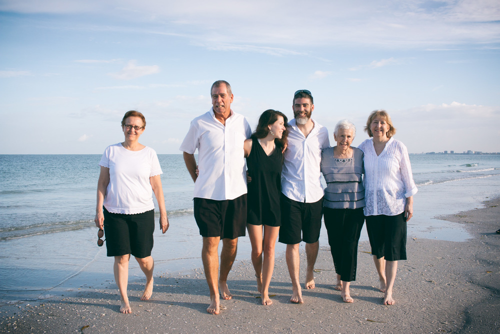 A Pass-a-Grille Beach candid family photo - the family walks and smiles barefoot in the wet sand.