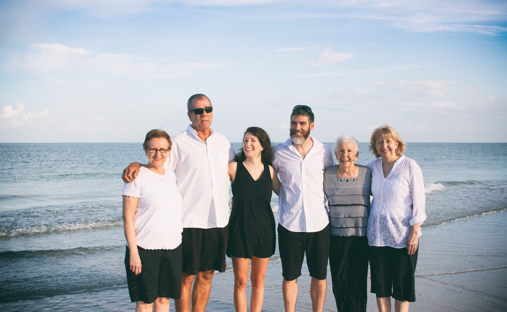 A more formal/traditional Tampa Bay area family portrait photo along the coastline.