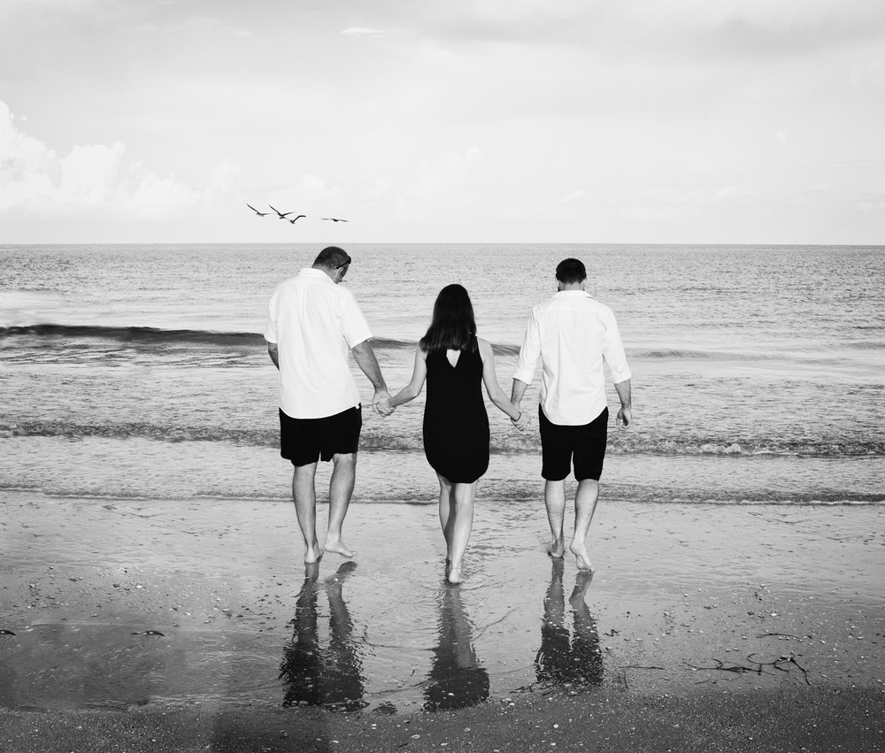 An artistic portrait of father, daughter and daughter's husband walking along Pass-a-Grille Beach