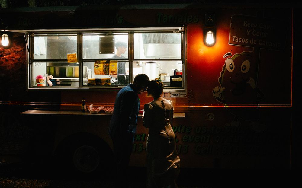 Bride and groom share a quiet moment by the taco truck.