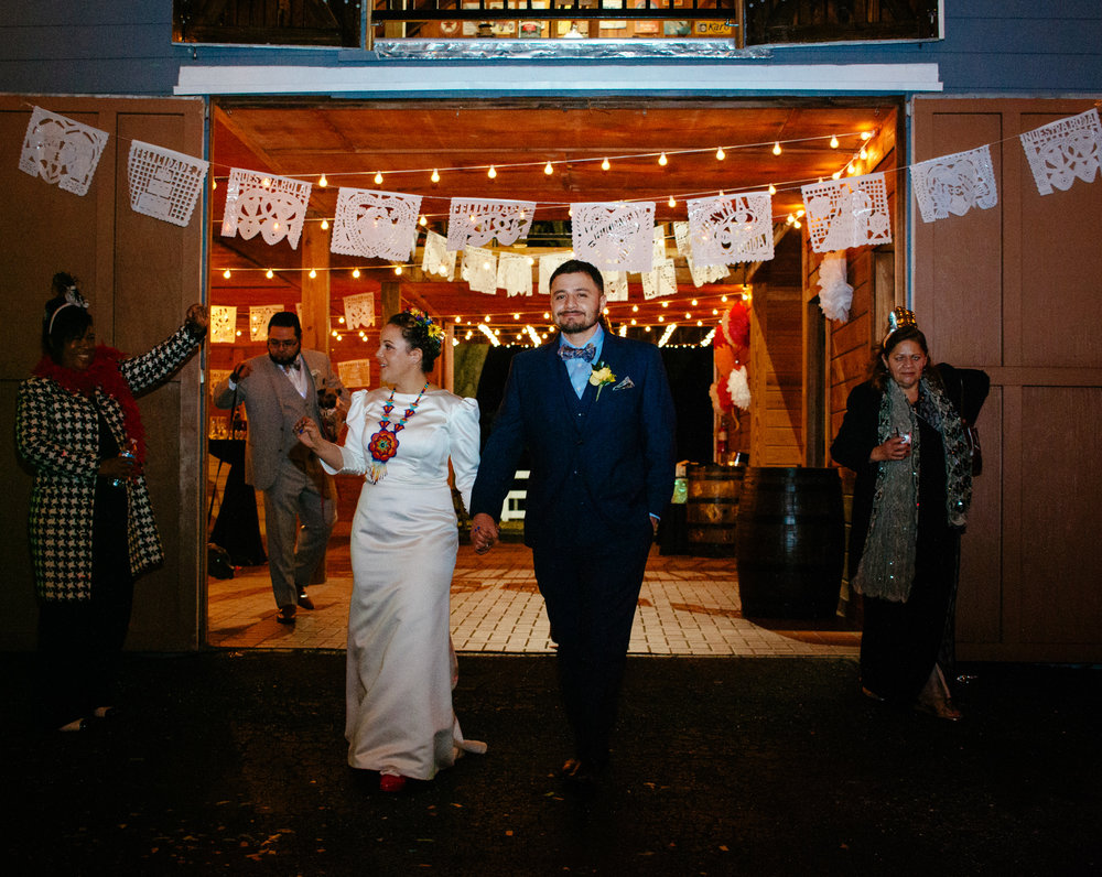 Bride and groom exit the brightly lit venue with joyous smiles.