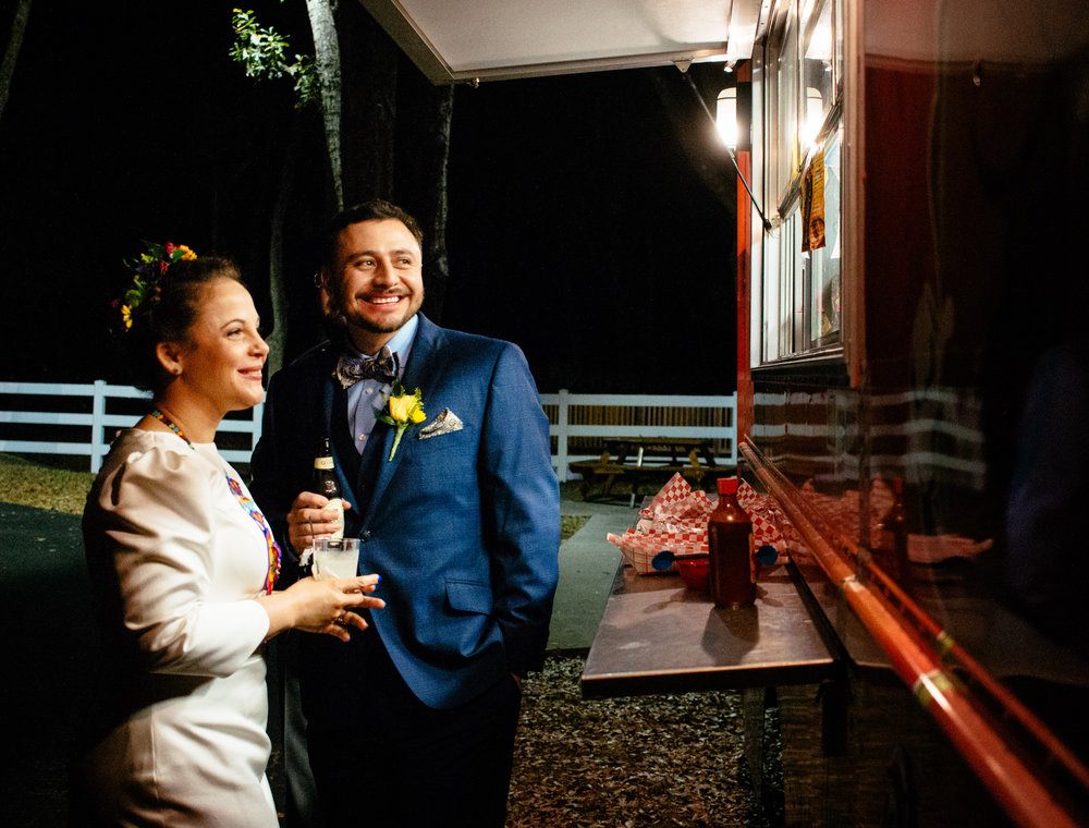 Bride and groom share a sweet moment by the taco truck.