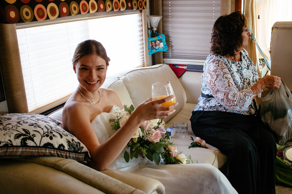 A happy bride smiles and drinks her mimosa after the ceremony.