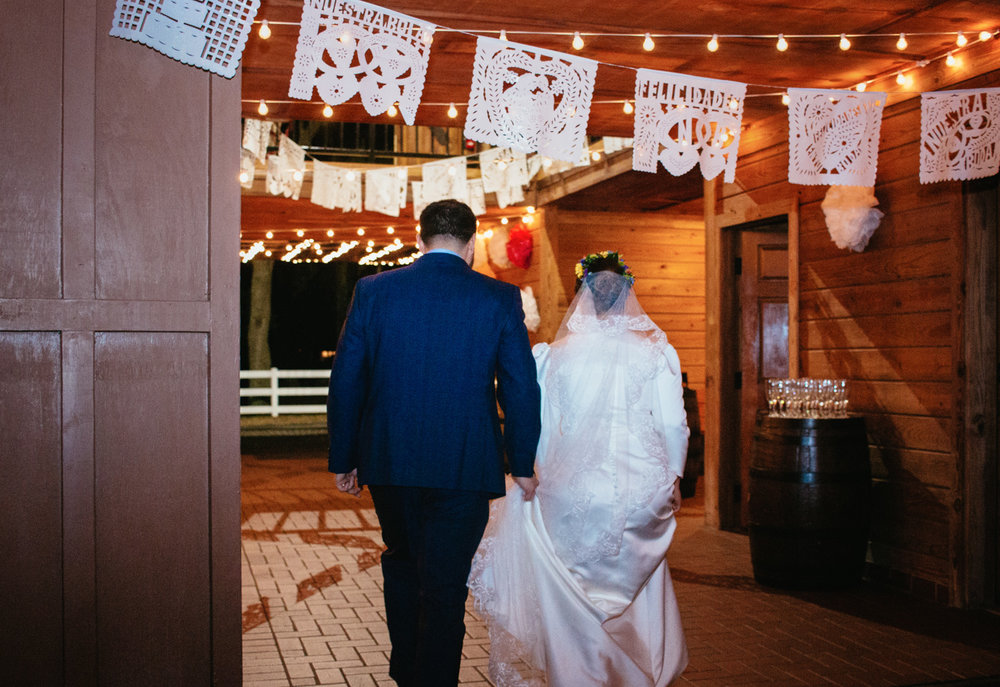 Bride and groom walk through the barnyard venue hand in hand.