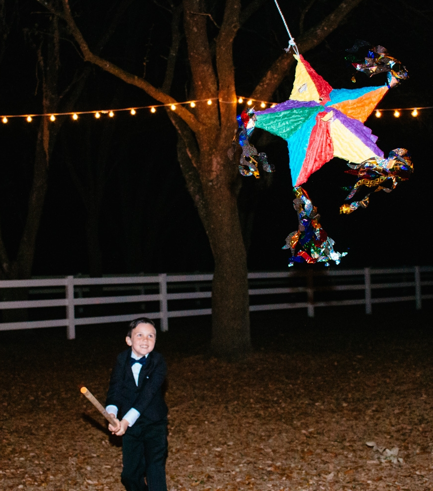 A tiny tuxedo-clan wedding guest swings at a colorful pinata.