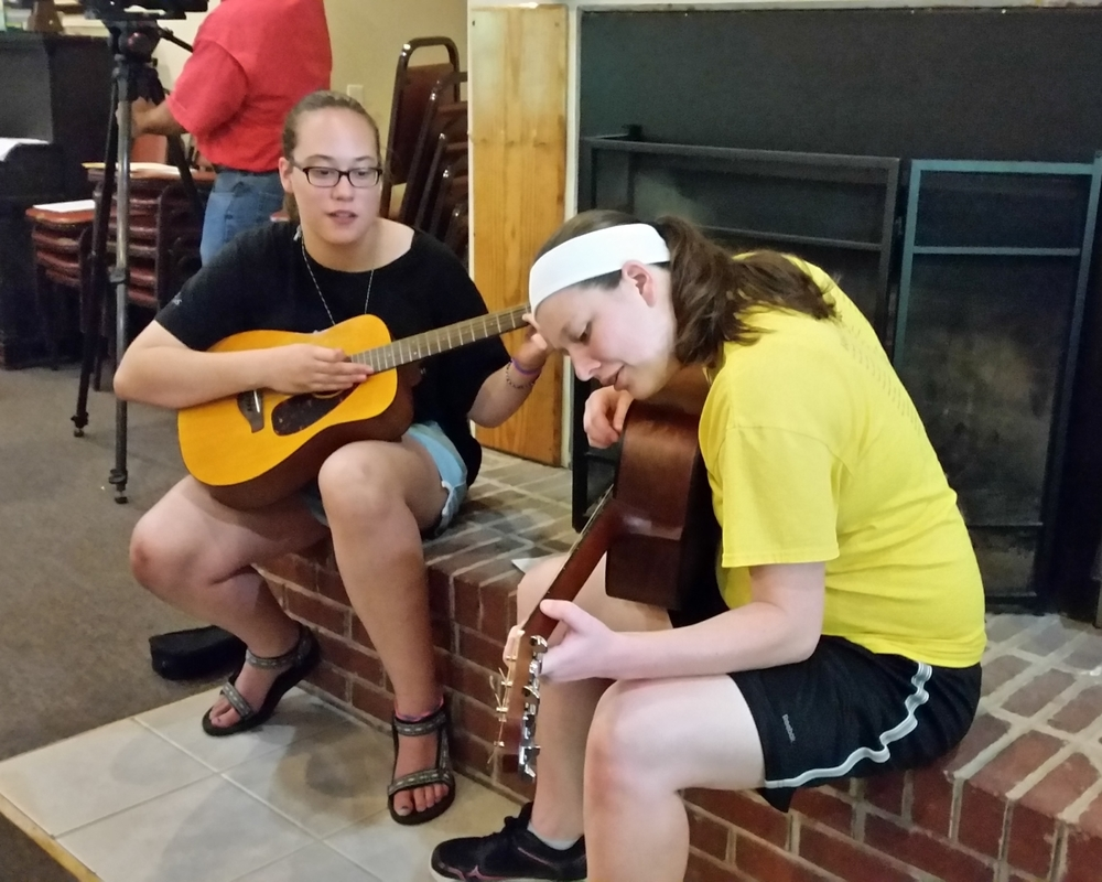Whitley (right) demonstrates chords to a Youth Folk camper.